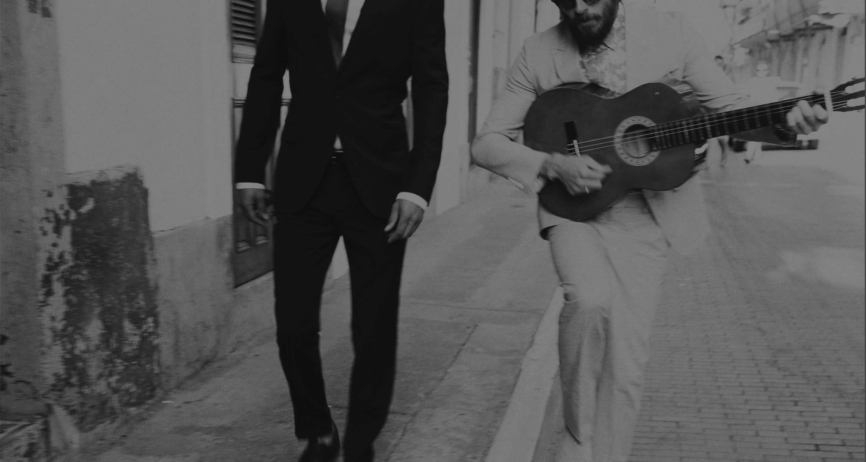 Man in suit next to man with guitar