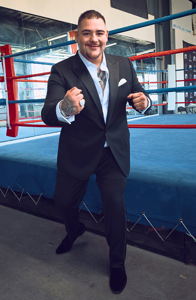 Andy taking a boxing stance in a Bonobos suit next to the boxing ring