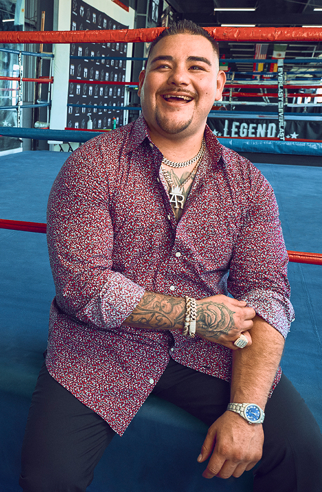Andy sitting on the boxing ring wearing a floral Bonobos shirt