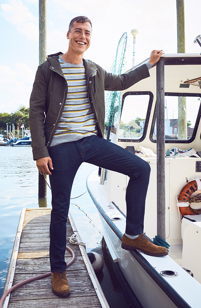 Brandon Sewall standing with one foot on his boat by the dock