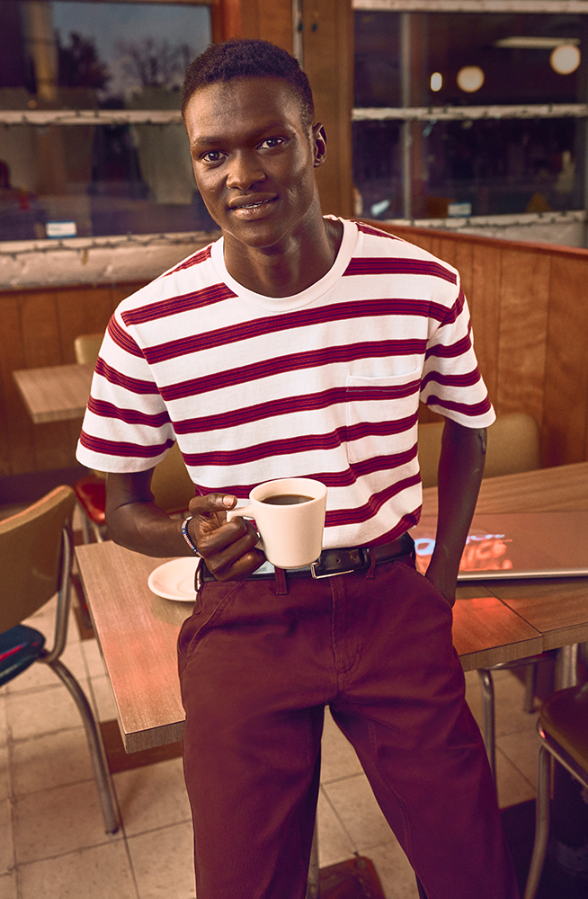 Lual standing in a diner holding a cup of coffee