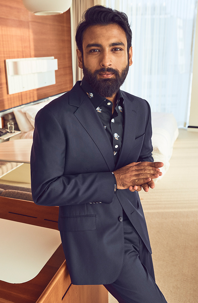 Tirthak sitting in a hotel room wearing a Bonobos suit