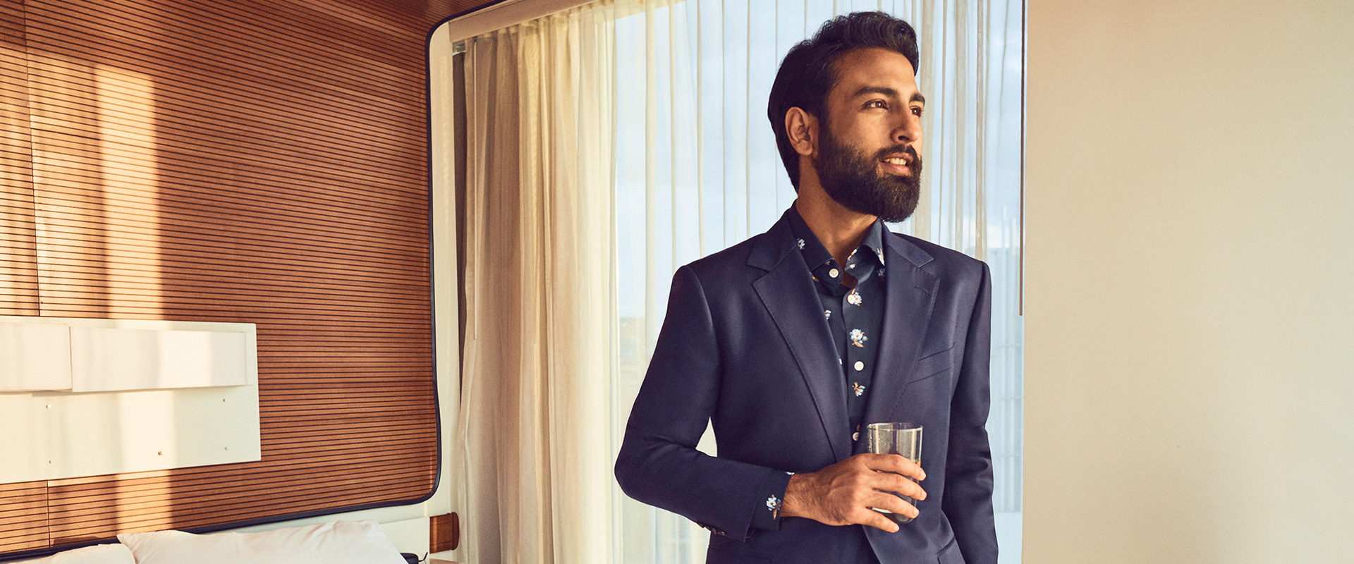 Tirthak standing in a hotel room wearing a Bonobos suit